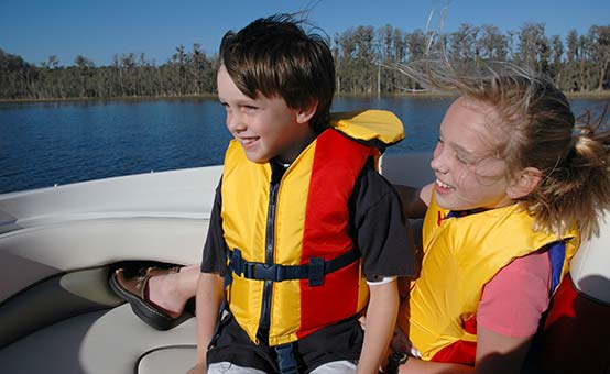 boy girl children wearing proper life jackets on a boat