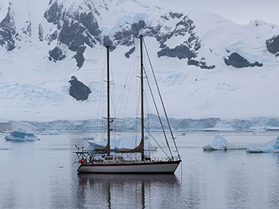 Sailboat cruises through icy water