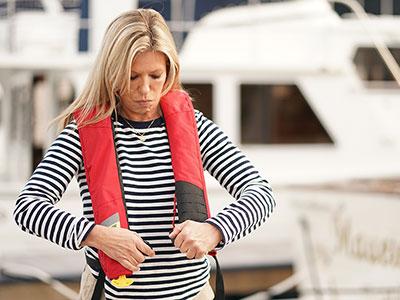 female boater wearing life jacket PFD DAN Boater