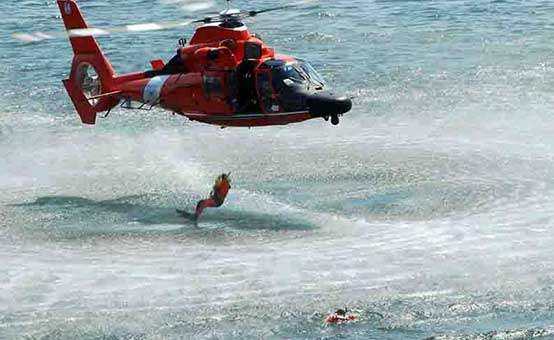 Coast Guard rescue divers jumping from helicopter into the ocean