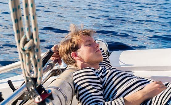 male sailor sleeping aft on the yacht