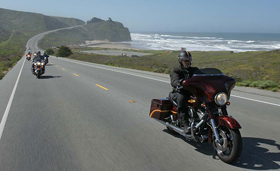 motorcycle riders cruising seaside highway