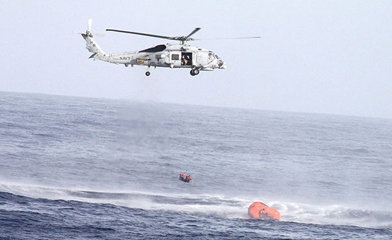 US Navy helicopter hovers above a life raft while performing a search and rescue operation