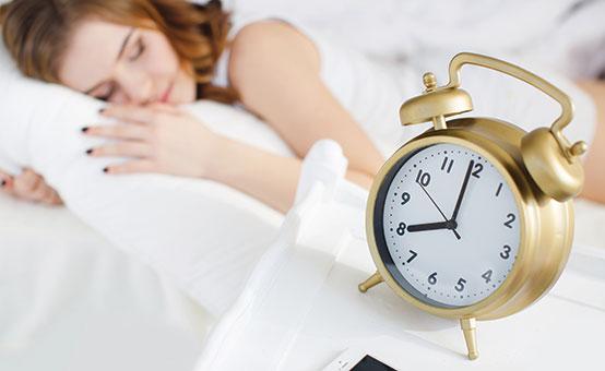 jet lagged woman sleeping with alarm clock